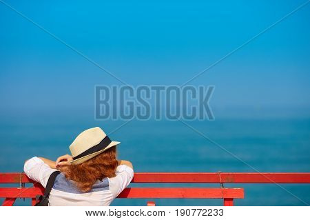 Young redhead woman in hat on pier looks out into ocean with copy space