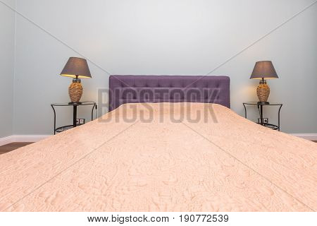 Comfortable bed with two lamps and beige blanket