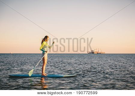 Perfect slim woman stand up paddle surfing with beautiful sunset or sunrise colors