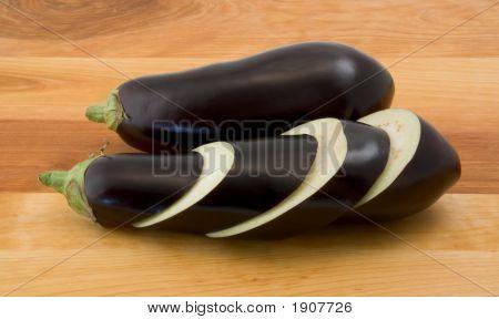 Whole And Sliced Eggplants On Wood Table