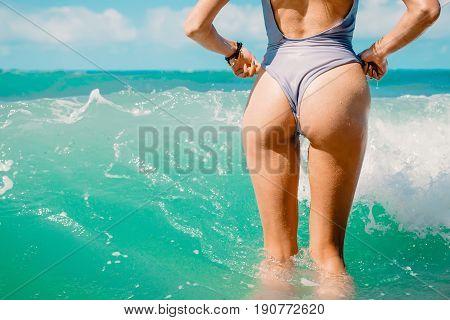 Slim luxury girl in a bikini swimming in ocean. Perfect tanned body, perfect figure