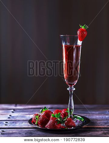 Glass of pink champagne on a wooden table. Strawberries on a metal plate nearby. Selective focus. The atmosphere of evening and romance. Delicious dessert