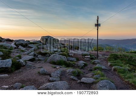 French countryside - Vosges. Hiking trail at sunrise with a signpost and a breathtaking view of the Rhine valley  and the Black Forest in the background.