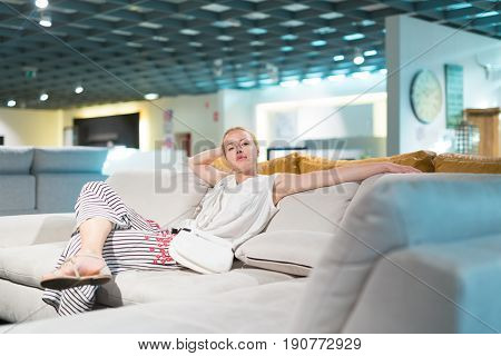 Caucasian woman shopping for furniture, sofa and home decor in store. Lady sitting on couch imagining her new home architectural arrangement.