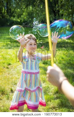 Little girl catching rainbow soap bubbles in green park when one of them breaks.