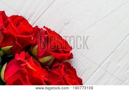 Few red roses in a corner on light wooden background with copyspace top view