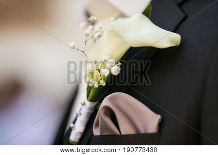 A Boutonniere Made Of Calla And Tiny Daisies Pinned To Black Tuxedo