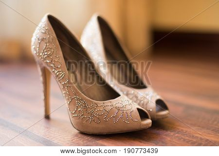 Open Toe Beige Shoes Decorated With Crystals Stand On The Floor