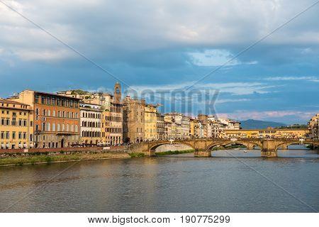Ponte Santa Trinita or St Trinity Bridge a renaissance bridge in Florence Italy. It is spanning over Arno river with Ponte Vecchio on background. Sunset.
