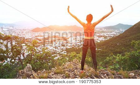 Woman runner raise hands up in the air. Female run on top of the mountain, cheering in winning gesture. 4K