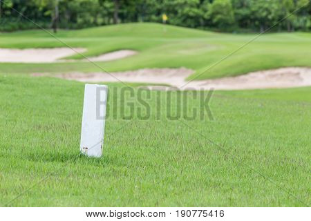 The white distance marker pole to inform range of golfing with blurred green golf course.