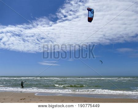 Castricum, The Netherlands - June 10, 2017: Young Woman Handling Her Kite While Standing In Shallow