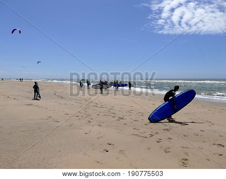 Castricum, The Netherlands - June 10, 2017: Young Teenagers Having Fun With Surfing Lessons Carrying