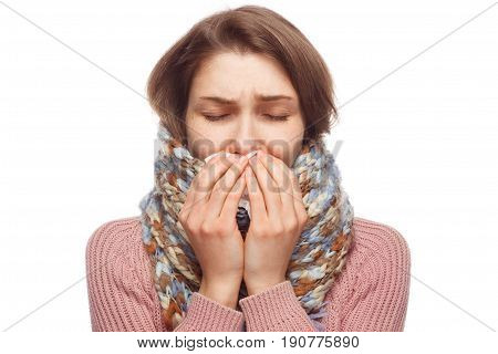 Young woman cuddling in scarf and sneezing with eyes closed on white background.