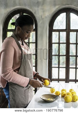 African descent woman grating lemon rind