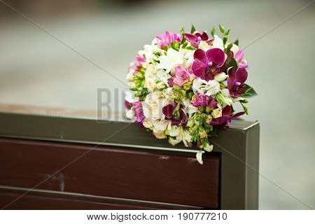 Brige and violet wedding bouquet lies on the back of a bench