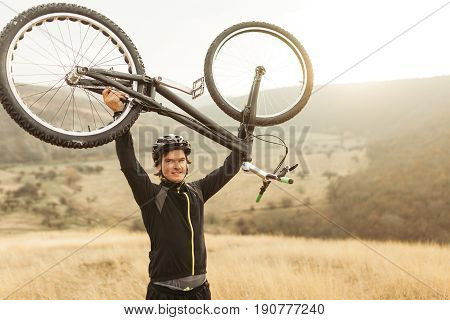 Young male in sportswear standing among plain and mountains and holding mountain bike above head.