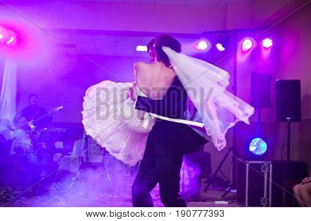 Groom Whirls A Bride In A Smoke On The Dancefloor
