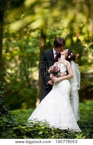 Fiance Kisses A Tiny Bride Standing In The Forest