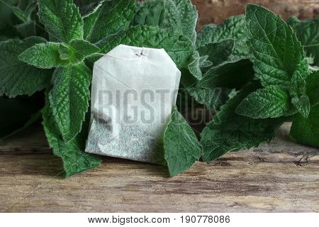 A packet of tea on a mint background on a wooden background