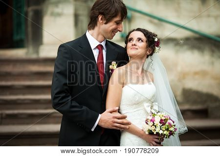 Fiance Holds Bride's Elbow Tender Looking At Her With Love