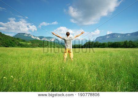 Man and green meadow in mountain. Conceptual design.