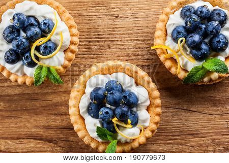 Delicious Blueberry tartlets with vanilla cream on the wooden background. Top view.