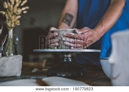 Close up of male hands working with clay on artisan working stand from dry wood surrounded by artistic workshop tools and implements creates poterry diy