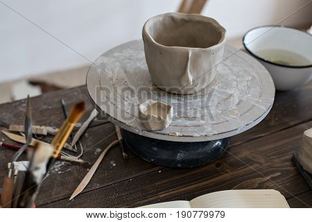 Close up of still life fresh clay pot for flowers or accessories carefully and lovingly carved out of fresh mud material artisan hand made piece with tools and brushes around