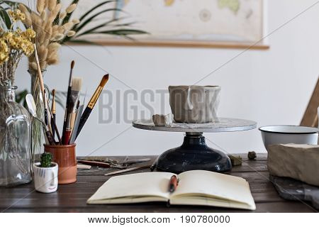 Close up of still life fresh clay pot for flowers or accessories carefully and lovingly carved out of fresh mud material open clean notebook in front and world map in background