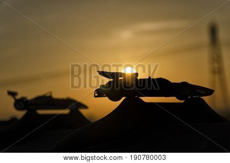 View of two historic cars with sunset in background