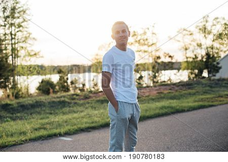 Sunset light photo with analog camera effect of handsome american man in sport casual outfit looking on photographer and smirking in beautiful sun lens flare