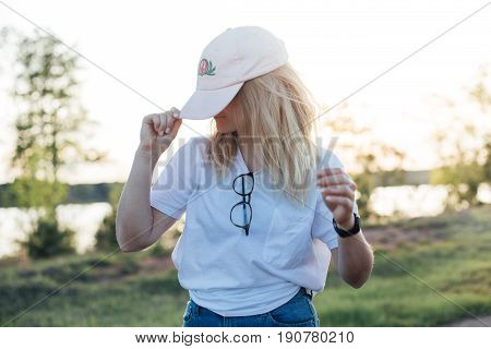 Beautiful attractive blonde female puts down university cap hat looks down shy and dancing to beat in amazing summer sunset light