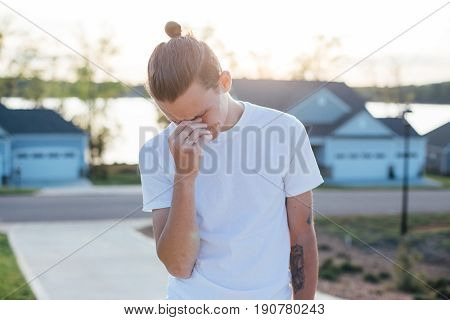 Handsome young male with a man bun is about to break out and cry sad and disappointment in life and choices in beautiful sunset light outdoors