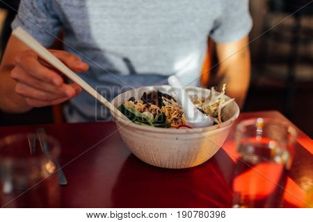 Soft focused shot of vegeterian vegan asian fusion dish with authentic natural ingridients in fancy downtown cafe restaurant hipster man eating with chopsticks