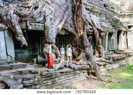 Family mother and kids at ancient Preah Khan jungle temple in Angkor Archeological area in Cambodia