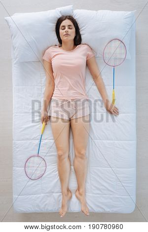 Sports games. Attractive peaceful brunette woman lying in her bed and having badminton rackets in her hands while enjoying this game