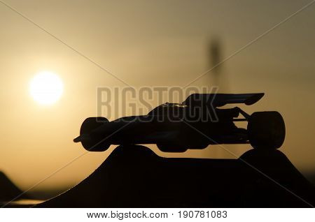 Outline of classic racing car with sunset in background