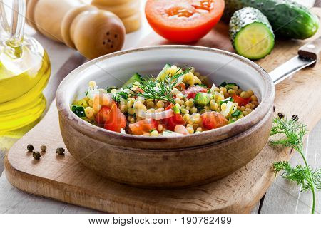 Salad made of couscous with vegetables in a bowl for healthy meal. Cooking of traditional Israeli Ptitim for lunch. Moroccan food and ingredients on a table.