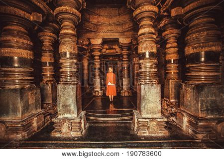 Lonely woman standing in center of ancient Hindu temple with stone columns, India. Traditional architecture of Asia