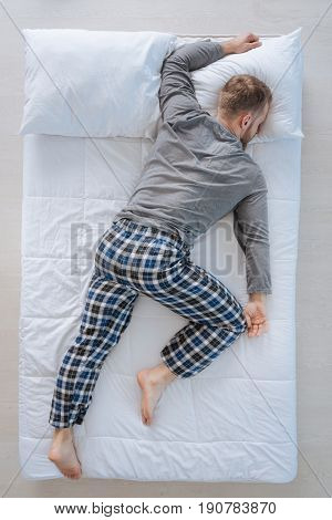 Comfortable position. Nice adult good looking man lying on his belly and sleeping while feeling comfortable