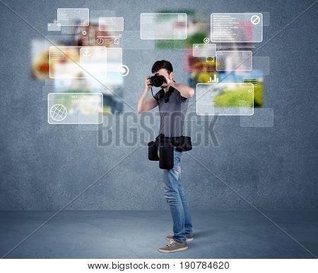 A young professional male photographer holding cameras and taking pictures in front of a blue wall with pictures, icons, text information concept