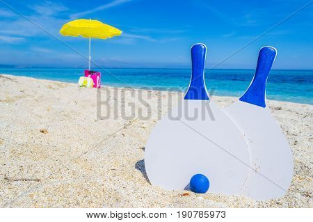 Beach rackets and parasol on the sand