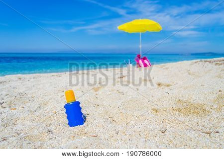 suntan lotion bottle and beach umbrella on the sand