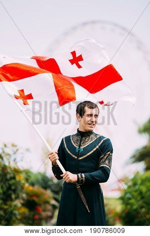 Batumi Adjara Georgia - May 26 2016: Young man in Georgian national dress holding a national flag in celebration of the national holiday - the Independence Day of Georgia.