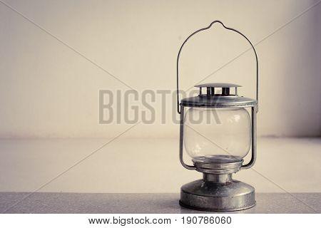 Vintage kerosene oil lantern lamp standing on cement floor with white wall background. (Vintage filter effect)