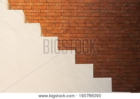Business Success Concept : Side view of white empty stairs with brown brick wall background. (Autumn filter effect)