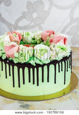 Celebratory cake with roses made of cream Chocolate streaks on a white wooden background.