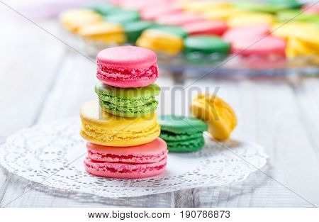 Colorful tasty macaroons on napkin natural light selective focus. Sweet and colorful dessert close up.