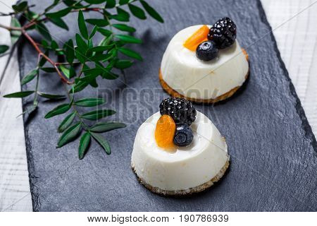 Mini cakes with dried apricots and blackberries on stone slate background close up. Homemade baking.